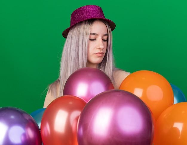 Pensando giovane bella donna che indossa cappello da festa in piedi dietro palloncini isolati sul muro verde