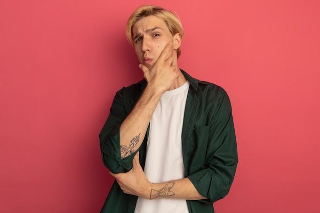 Думающий молодой блондин в зеленой футболке, положив руку на подбородок