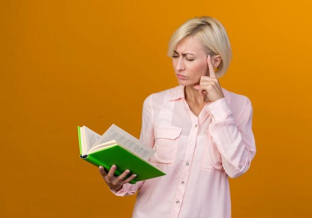 Pensando giovane bionda donna slava tenendo e guardando il libro mettendo il dito sulla guancia isolato sulla parete arancione