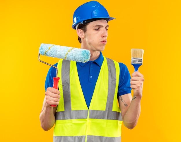 Pensare giovane costruttore in uniforme che tiene e guarda la spazzola a rullo con il pennello