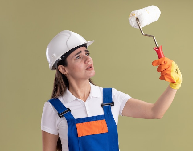 Thinking young builder woman in uniform and gloves raising and looking at roller brush isolated on olive green wall