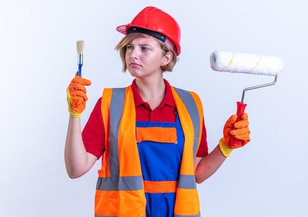 Pensando giovane donna costruttore in uniforme tenendo la spazzola a rullo e guardando il pennello in mano isolata sul muro bianco