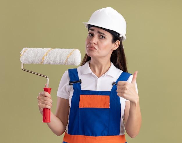 Giovane donna di pensiero del costruttore in uniforme che tiene la spazzola del rullo e che mostra il pollice in su isolato sulla parete verde oliva
