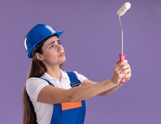 Pensando la giovane donna del costruttore in uniforme che alza e che guarda il mini rullo di vernice isolato sulla parete viola