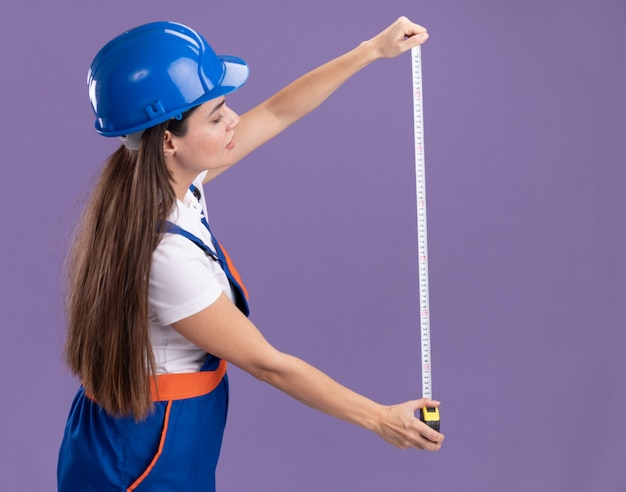 Thinking young builder woman in uniform stretching out tape measure isolated on purple wall