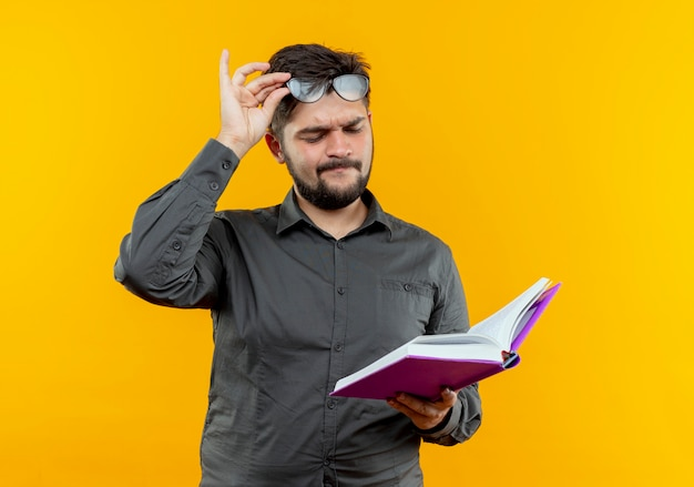 Думающий молодой бизнесмен в очках, держащий и смотрящий на книгу на желтом