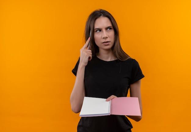 La giovane ragazza caucasica di pensiero che porta la maglietta nera che esamina il taccuino della tenuta del lato ha messo la penna sulla testa sulla parete arancione isolata