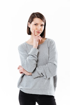 Thinking young caucasian woman standing isolated
