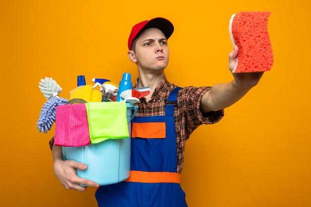 유니폼을 입고 모자를 쓰고 청소 도구 양동이를 들고 손에 스폰지를 보고 있는 생각하는 젊은 청소 남자
