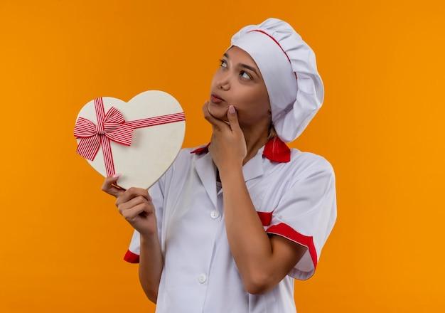 Pensando giovane cuoco femmina che indossa lo chef uniforme tenendo la scatola a forma di cuore mettendo la mano sul mento isolato su sfondo arancione