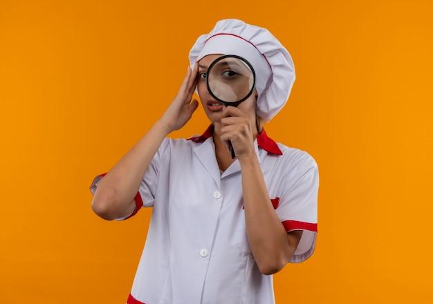 拡大鏡でカメラを見て、孤立したオレンジ色の背景に額に手を置くシェフの制服を着た若い料理人の女性を考える