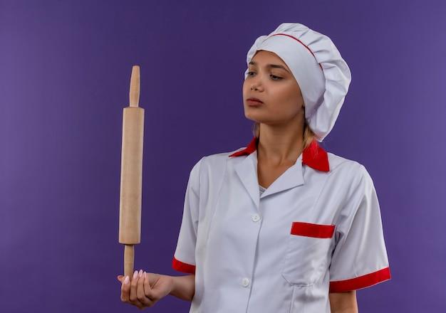 孤立した背景に彼女の手で麺棒を見てシェフの制服を着た若い料理人の女性を考える