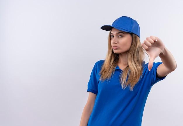 파란색 유니폼을 입고 젊은 배달 소녀를 생각하고 복사 공간이 흰 벽에 고립 된 그녀의 엄지 손가락 아래로 모자