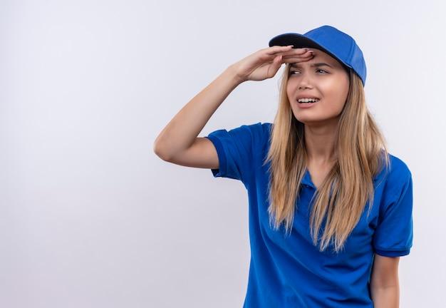 Pensando la giovane ragazza di consegna che indossa l'uniforme blu e il berretto guardando la distanza con la mano isolata su bianco