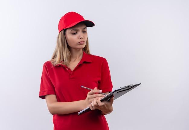 赤い制服とキャップを身に着けている思考の若い配達の女の子は、白で隔離クリップボードに書き込みます