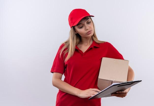 Pensando la giovane ragazza di consegna che indossa l'uniforme rossa e la scatola della tenuta del cappuccio e guardando la lavagna per appunti in mano isolata su bianco