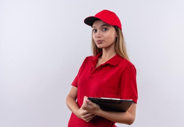 Pensare la giovane ragazza di consegna che indossa l'uniforme rossa e la lavagna per appunti della tenuta del cappuccio isolata su bianco
