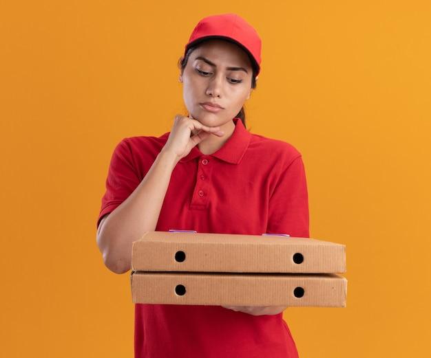 Pensando che la giovane ragazza di consegna indossa l'uniforme e la tenuta del cappuccio e guardando le scatole per pizza mettendo la mano sotto il mento isolato sulla parete arancione