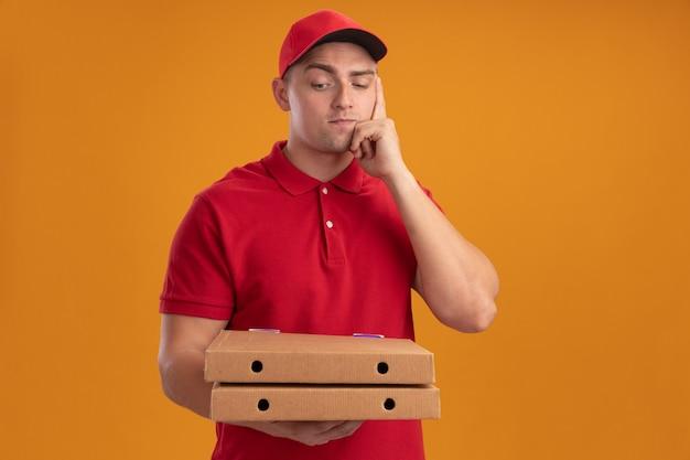 Pensando giovane fattorino che indossa l'uniforme con il cappuccio che tiene e guarda le scatole della pizza isolate sulla parete arancione