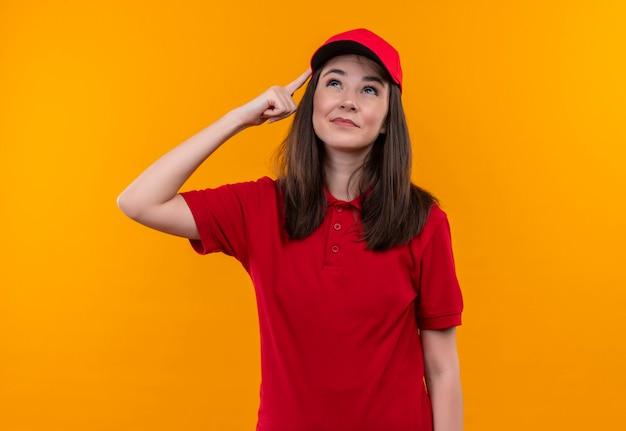 孤立したオレンジ色の壁に赤い帽子に赤いtシャツを着ている若い配達の女性を考えてください。
