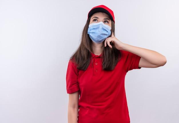 赤い帽子に赤いtシャツを着ている若い配達の女性を考えて孤立した白い壁にフェイスマスクを着ています。