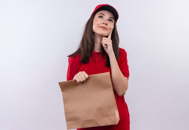 Pensando la giovane donna di consegna che indossa la maglietta rossa in berretto rosso che tiene un pacchetto sulla parete bianca isolata