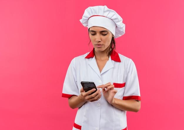 Pensando giovane donna cuoco che indossa il numero di composizione uniforme del cuoco unico sul telefono con lo spazio della copia