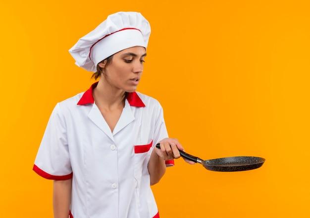 コピースペースのあるフライパンを持って見ているシェフの制服を着た若い女性料理人を考える