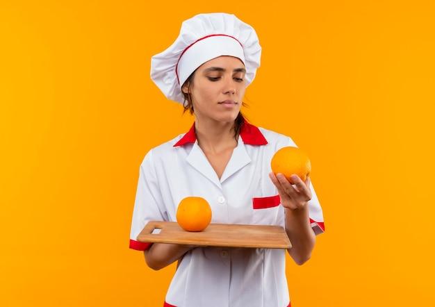 コピースペースのまな板の上にオレンジを持って見ているシェフの制服を着て若い女性料理人を考える