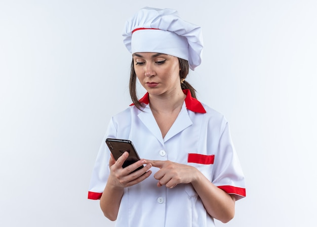 흰색 벽에 격리된 전화기를 들고 보고 있는 요리사 유니폼을 입고 생각하는 젊은 여성 요리사