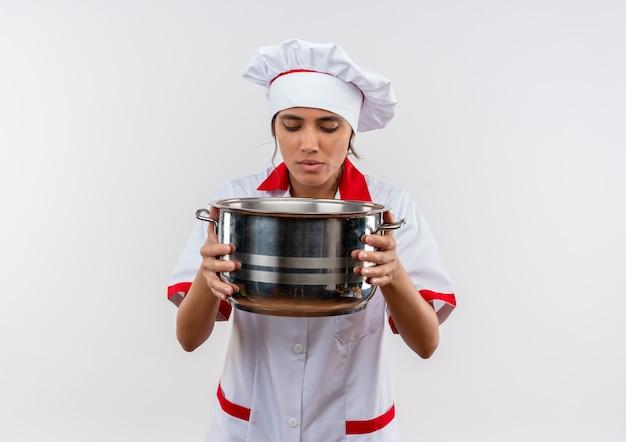 コピースペースのある鍋を持って見ているシェフの制服を着た若い女性料理人