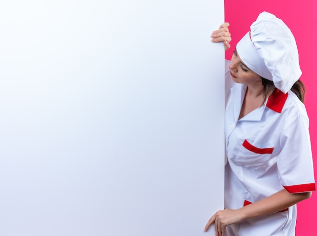 요리사 유니폼을 입고 생각 젊은 여성 요리사 복사본 공간이 분홍색 벽에 고립 된 흰 벽 근처에 서