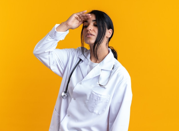 노란색 배경에 격리된 손으로 먼 곳을 바라보는 청진기가 달린 의료 가운을 입은 생각하는 젊은 여성 의사