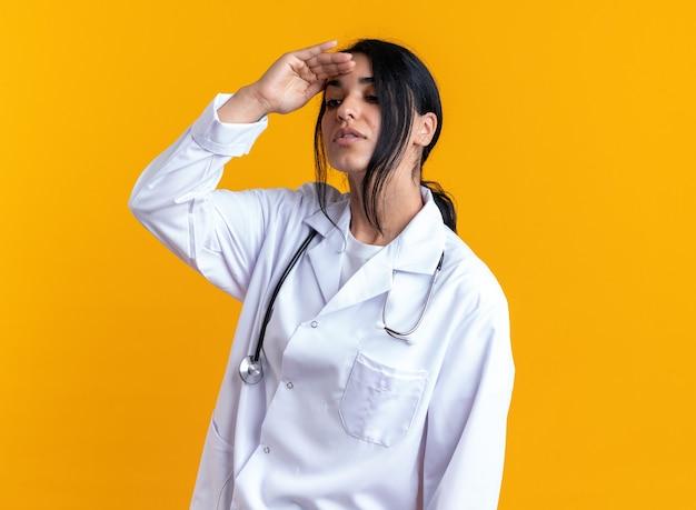 Pensando giovane dottoressa indossando accappatoio medico con stetoscopio guardando a distanza con la mano isolata su sfondo giallo