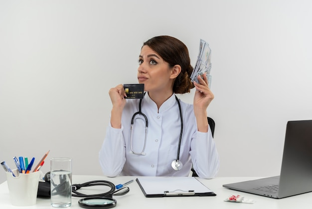 Thinking young female doctor wearing medical robe with stethoscope sitting at desk work on computer with medical tools holding cash and credit card with copy space