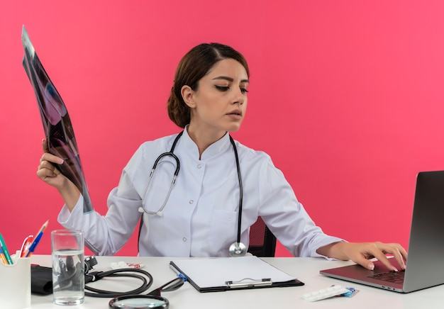 Thinking young female doctor wearing medical robe with stethoscope sitting at desk work on computer with medical tools holding x-ray and used laptop with copy space
