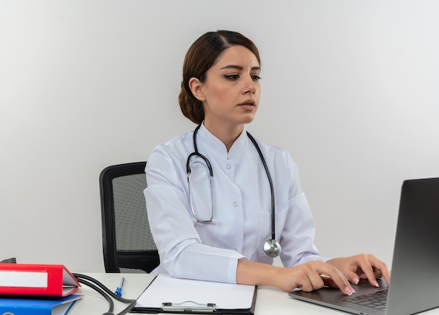 Thinking young female doctor wearing medical robe with stethoscope sitting at desk work on computer with medical tools used laptop with copy space