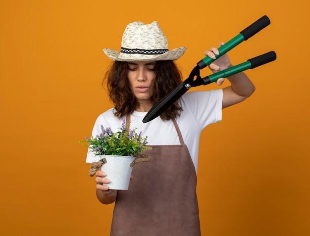 バリカンで植木鉢に花を切る園芸帽子を身に着けている制服を着た若い女性の庭師を考える