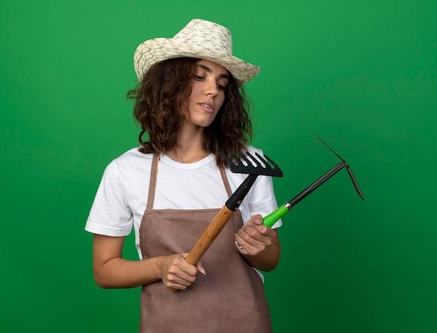 ガーデニング帽子をかぶって、くわ熊手で熊手を見て制服を着た若い女性の庭師を考える