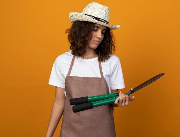 Pensando giovane giardiniere femminile in uniforme che indossa cappello da giardinaggio tenendo e guardando i clippers