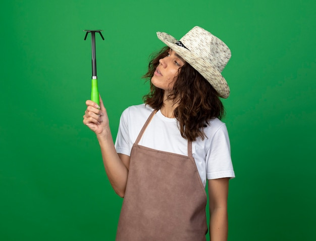 Thinking young female gardener in uniform wearing gardening hat holding and looking at hoe rake