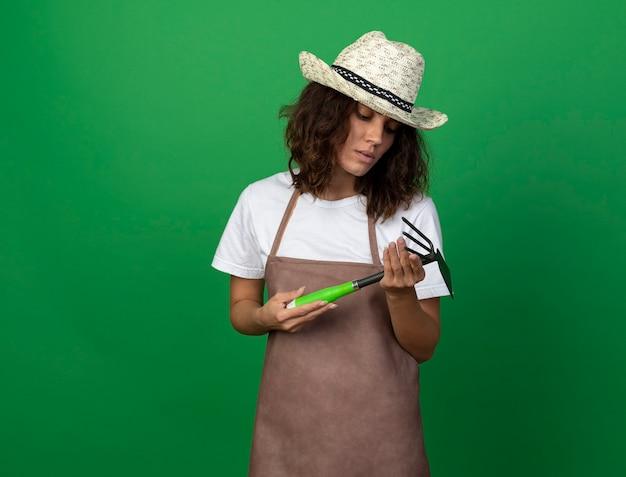 Pensando giovane giardiniere femminile in uniforme che indossa cappello da giardinaggio tenendo e guardando zappa rastrello