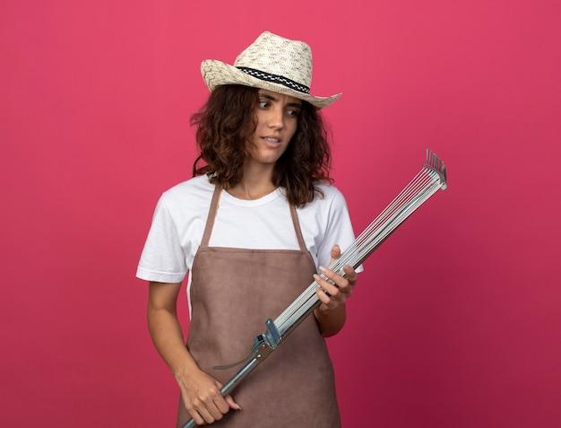 Pensando giovane giardiniere femminile in uniforme che indossa cappello da giardinaggio tenendo e guardando il rastrello di foglia