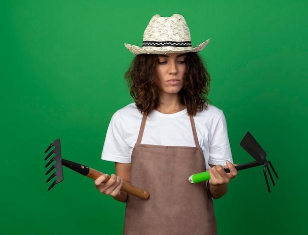 Pensando giovane giardiniere femminile in uniforme che indossa cappello da giardinaggio tenendo e guardando rastrello con zappa rastrello