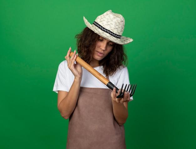 Pensando giovane giardiniere femminile in uniforme che indossa cappello da giardinaggio tenendo e guardando il rastrello