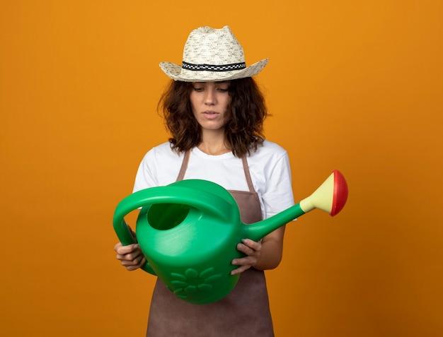 Pensando giovane giardiniere femminile in uniforme che indossa cappello da giardinaggio tenendo e guardando annaffiatoio