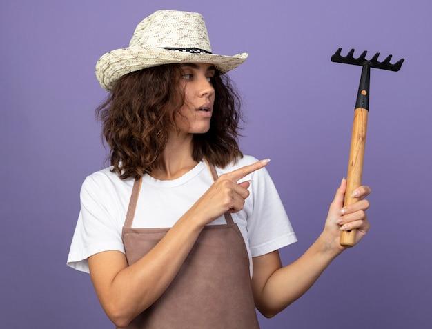 Pensando giovane giardiniere femminile in uniforme che indossa cappello da giardinaggio holding e punti al rastrello