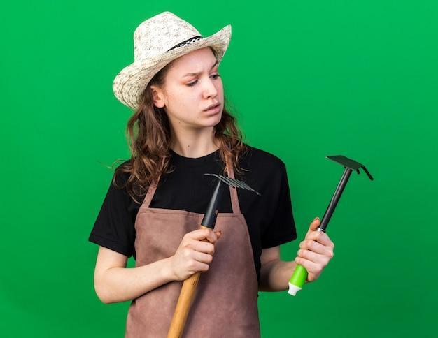 녹색 벽에 괭이 갈퀴가 있는 갈퀴를 들고 원예용 모자를 쓰고 생각하는 젊은 여성 정원사