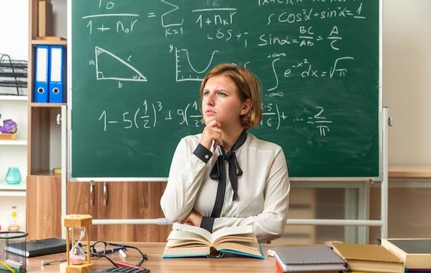 思考の若い女教師が教室で学校の道具で顎をつかんでテーブルに座っている