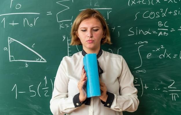 Pensando giovane insegnante femminile in piedi davanti alla lavagna tenendo e guardando il libro in classe